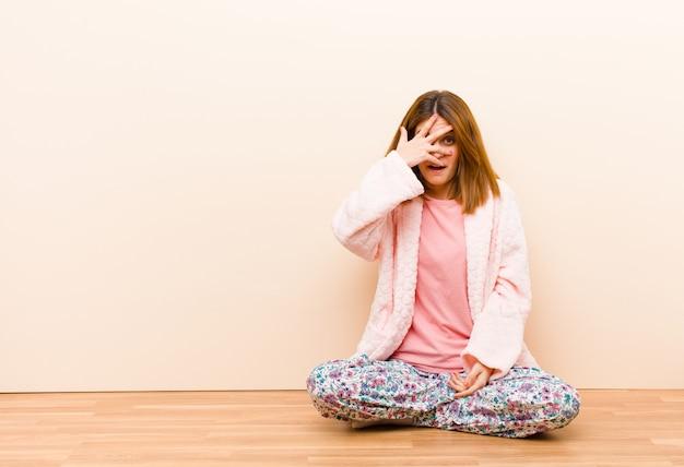 自宅で座っているパジャマを着た若い女性が見てショックを受けた、怖いまたは恐怖、手で顔を覆って、指の間を覗く
