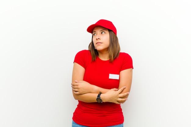 肩をすくめ、混乱し、不確かな感じの女性が腕を組んで疑い、白に対して困惑した表情