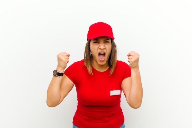 怒りの表現または拳を握りしめ白に対して成功を祝って積極的に叫んで配達の女性