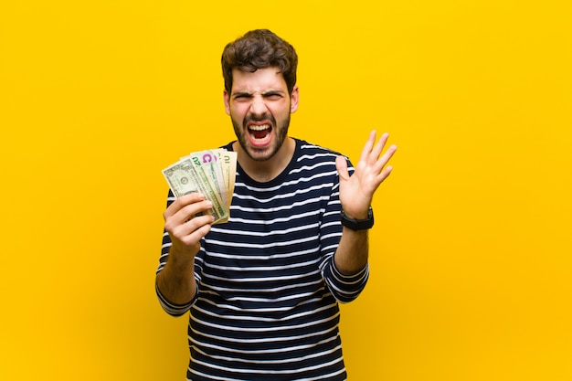 Молодой красавец с доллар банкноты против оранжевого му