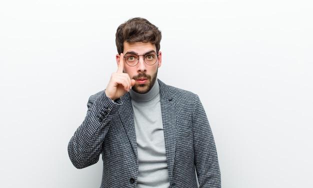 驚いて、口を開けて、ショックを受けて、新しい思考、アイデアを実現する、または白い壁に対して若いマネージャーの男