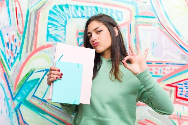 落書きの壁に対して若いきれいな女性