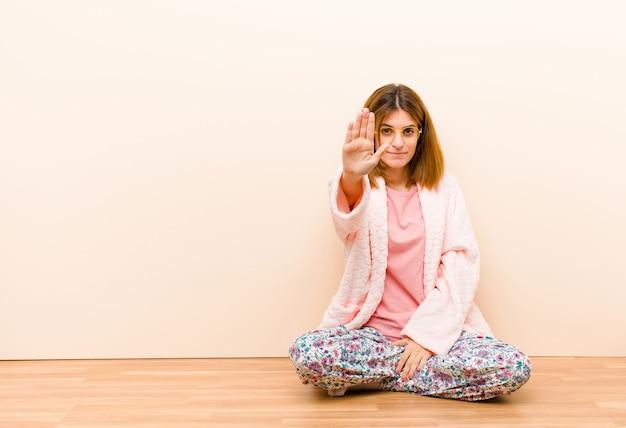 深刻な船尾に不満と怒って停止ジェスチャーを作る開いたやしを見せて自宅で座っているパジャマを着た若い女性