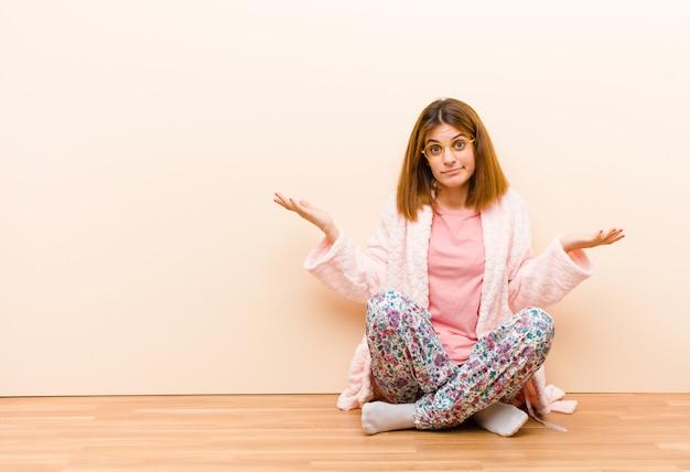 Молодая женщина в пижаме сидит дома и смотрит озадаченно смущенно и подчеркнуто удивляясь, что разные варианты чувствуют себя неуверенно