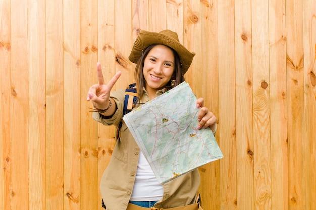 Молодая женщина путешественника с картой против деревянной стены