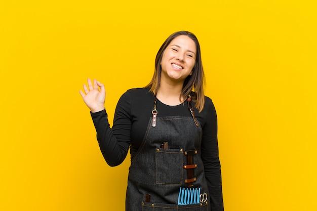 Парикмахер женщина улыбается счастливо и весело машет рукой приветствуя и приветствуя вас или прощаясь