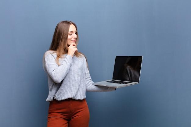 コピースペースで青い壁にラップトップを持つ若いきれいな女性