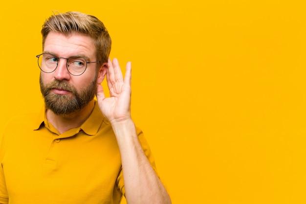 Молодой блондин человек выглядит серьезным и любопытным, слушая, пытаясь услышать секретный разговор или сплетни, подслушивая оранжевую стену