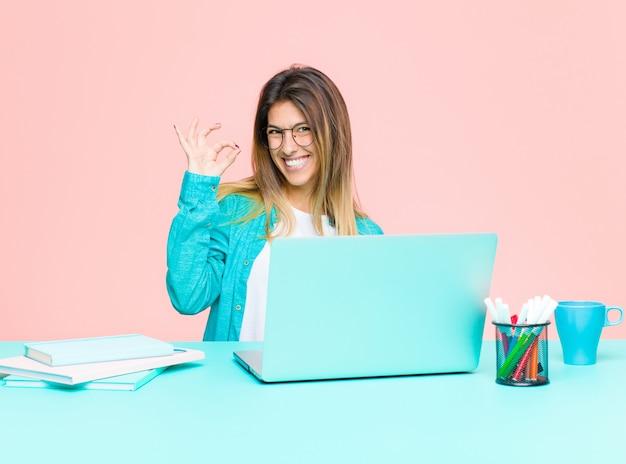若いきれいな女性の成功と満足感、口を大きく開けて笑って、手で大丈夫サインを作るラップトップでの作業