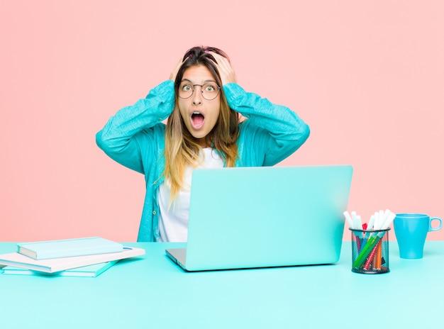 Молодая красивая женщина работает с ноутбуком, чувствуя себя в ужасе и шоке, поднимая руки к голове и паникуя по ошибке
