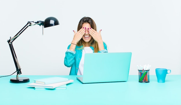 Молодая красивая женщина работает с ноутбуком, улыбаясь и чувствуя себя счастливым, закрыв глаза обеими руками и ожидая невероятного сюрприза