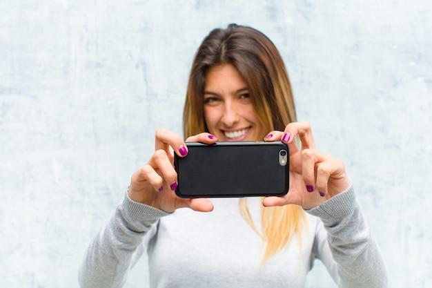 グランジの壁にスマートフォンを持つ若いきれいな女性