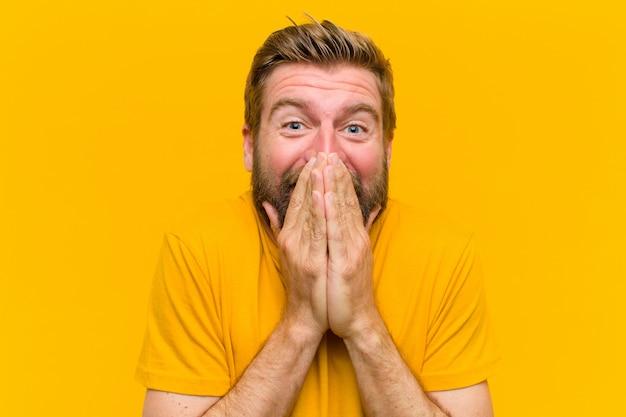 Молодой блондин человек, глядя счастливым, веселым, счастливым и удивленным охватывающий рот обеими руками