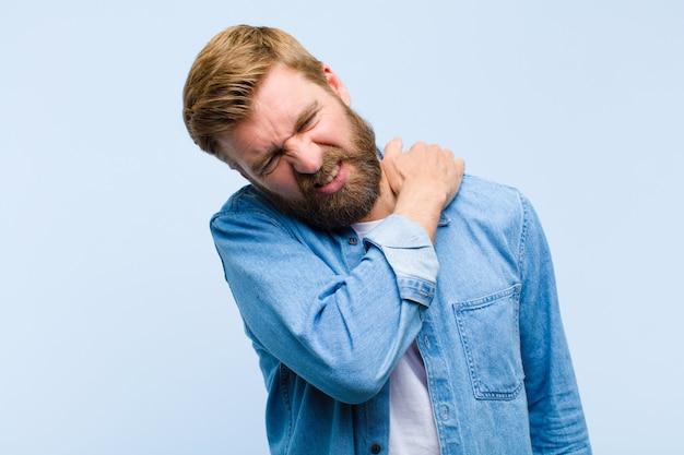 疲れを感じている若い金髪の成人男性は、背中や首の痛みで心配して欲求不満と落ち込んで苦しんで強調しました。