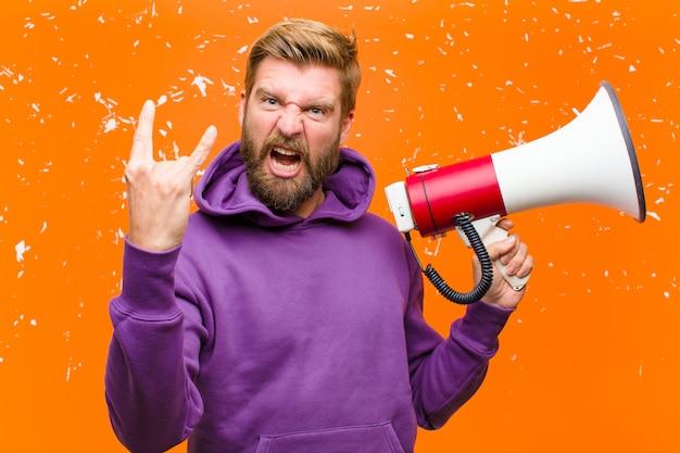 Молодой блондин с мегафоном в фиолетовой толстовке у поврежденной оранжевой стены