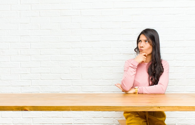 テーブルの前に座ってどの決定を下すのか疑問に思って、考えて、疑って混乱している、さまざまなオプションを持つ若いラテン女性