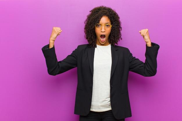 Молодая черная деловая женщина агрессивно кричала с сердитым выражением лица или сжала кулаки, празднуя успех