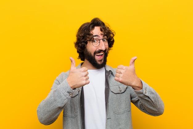 Молодой сумасшедший человек широко улыбается счастливым уверенно и успешно с обоими пальцами вверх