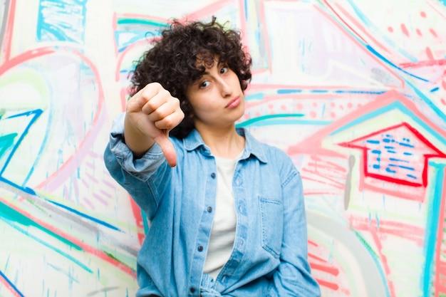 落書きの壁に対して深刻な表情で親指を下に示す怒っている腹を立てて失望または不満を感じる若いかなりアフロの女性