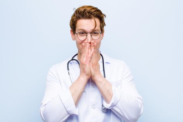 Молодой рыжий главный врач счастлив и взволнован, удивлен и поражен, покрывая рот руками, хихикающими с милым выражением на синей стене