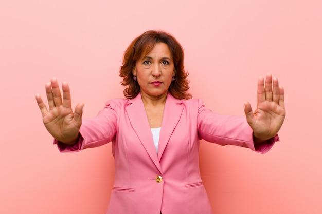 深刻な不幸な怒って不愉快なエントリを禁止または両方の開いた手のひらで停止と言って探している中年女性