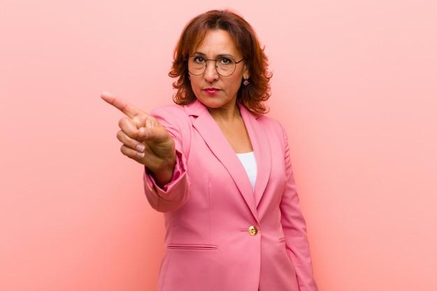 Женщина среднего возраста, раздраженная, мятежная и агрессивная, отбрасывает средний палец