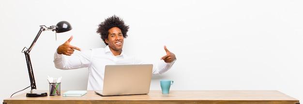 Молодой черный бизнесмен выглядит гордым, высокомерным, счастливым, удивленным и удовлетворенным, указывая на себя, чувствуя себя победителем на столе