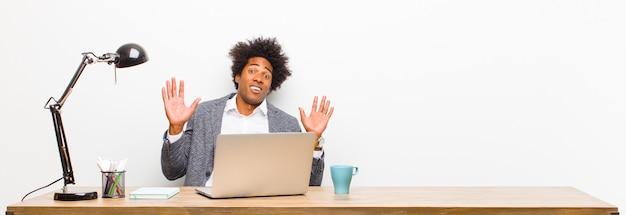 Молодой темнокожий бизнесмен, выглядящий нервным, взволнованным и обеспокоенным, говоря, что я не виноват или не сделал этого на столе
