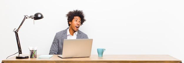 Молодой черный бизнесмен, чувствуя себя шокирован, счастлив, поражен и удивлен, глядя в сторону с открытым ртом на столе
