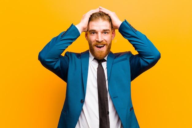 興奮して驚いて見ている若い赤い頭の実業家、頭に両手で口を開けて、幸運な勝者オレンジの壁のような感じ