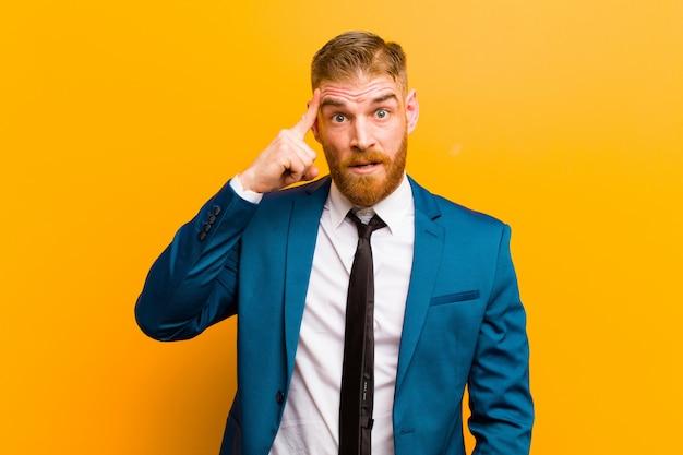 見てみるとビックリ、口を開けて、ショックを受けて、新しい思考、アイデアやコンセプトのオレンジ色の壁を実現する若い赤い頭の実業家
