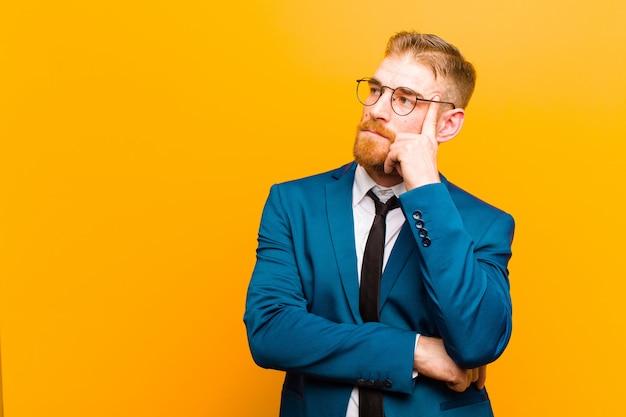 疑わしい表情で疑問に思って、オレンジ色の壁を見上げると、集中した表情で若い赤い頭の実業家