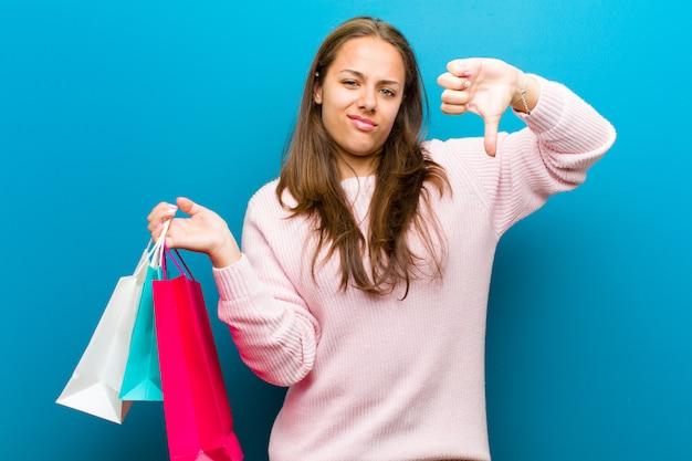 ショッピングバッグの青い壁を持つ若い女性