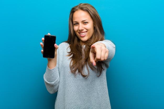 携帯電話の青い壁を持つ若い女性