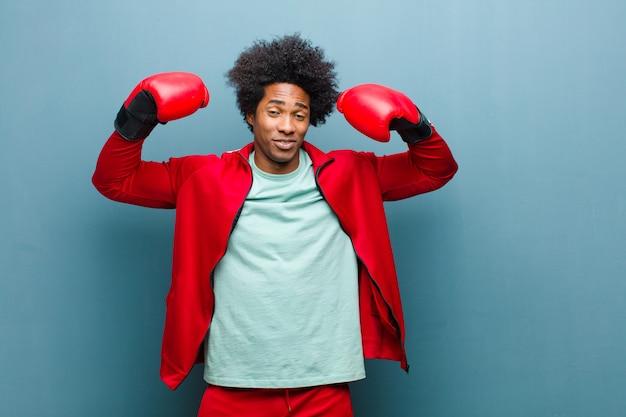 ボクシンググローブと若い黒人男性青いグランジ壁
