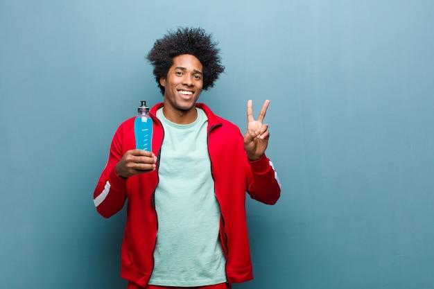 スポーツドリンクブルーグランジ壁を持つ若い黒人男性