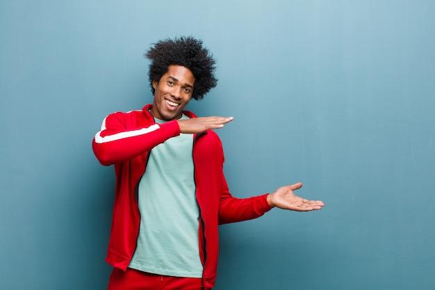 Молодой черный спортивный человек улыбается, чувствуя себя счастливым, позитивным и удовлетворенным, держа или показывая объект или концепцию на копии пространства против стены гранж