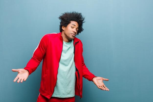 Молодой черный спортивный человек, чувствуя себя невежественным и растерянным, не подозревая, абсолютно озадачен тупым или глупым взглядом на гранжевой стене