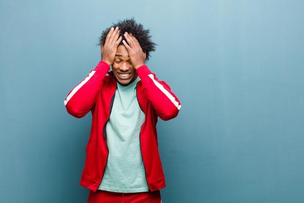 Молодой черный спортивный человек, чувствуя стресс и беспокойство, депрессию и разочарование от головной боли, поднимая обе руки к стене гранж