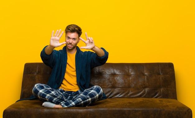 笑みを浮かべてフレンドリーに見えるパジャマを着ている若い男ソファに座って