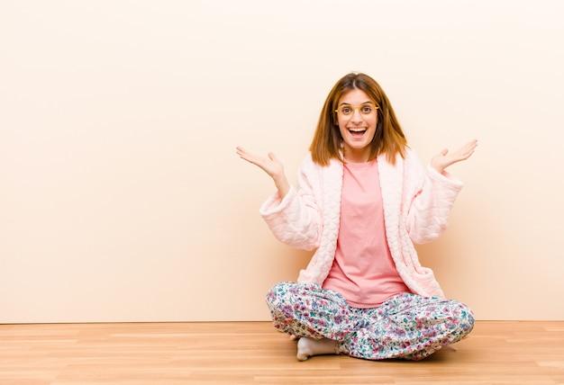 自宅で座っているパジャマを着た若い女性