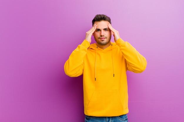 Молодой латиноамериканский человек с непринужденным взглядом на фиолетовой стене