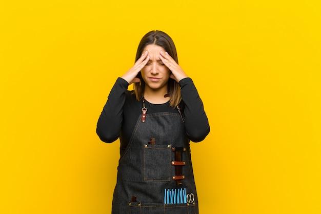 Женщина-парикмахер, выглядящая подчеркнутой и расстроенной, работающая под давлением с головной болью и обеспокоенная проблемами против оранжевой стены