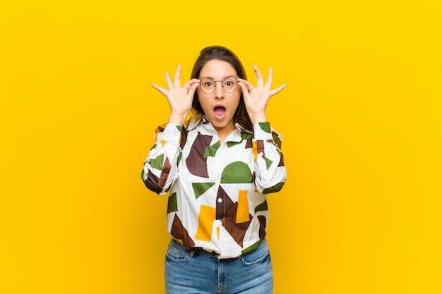 黄色の壁に対して隔離された驚いた、信じられない表情でメガネを保持しているショックを受け、驚いて、驚いたラテンアメリカの女性