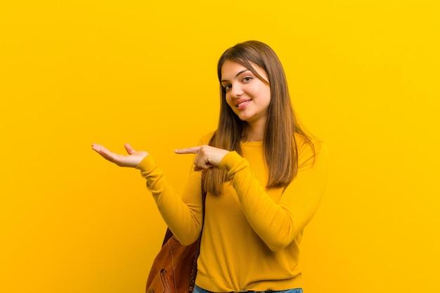陽気な笑顔と側の手のひらにコピースペースを指している、オレンジ色の壁に対してオブジェクトを表示または広告する若いきれいな女性
