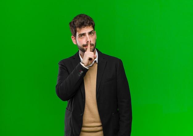 真面目な青年実業家と沈黙または静かを要求する唇に押された指でクロス、緑の壁に対して秘密を保つ