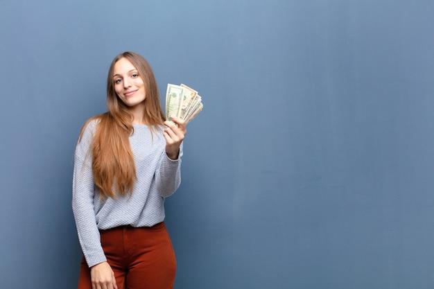Молодая милая женщина с банкнотами доллара против голубой стены с космосом экземпляра