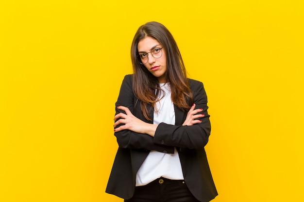 Молодая симпатичная женщина чувствует себя недовольной и разочарованной, выглядит серьезной, раздраженной и злой со скрещенными руками на оранжевой стене