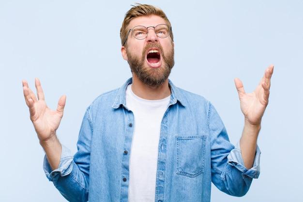 Молодая блондинка взрослый мужчина яростно кричит, чувствуя стресс и раздражение с поднятыми вверх руками, говоря, почему я