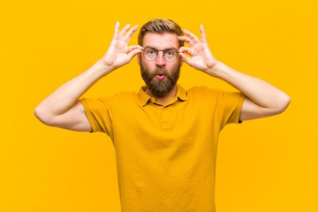 Молодой блондин, чувствуя себя потрясенным, изумленным и удивленным, держа очки с удивленным, не верящим взглядом на оранжевой стене